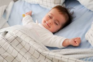 Bébé heureux les bras étendus en train de dormir dans sa chambre de bébé