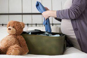 Femme enceinte en train de mettre des vêtements dans sa valise pour la maternité