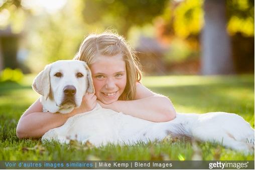 Petite fille caline un chien