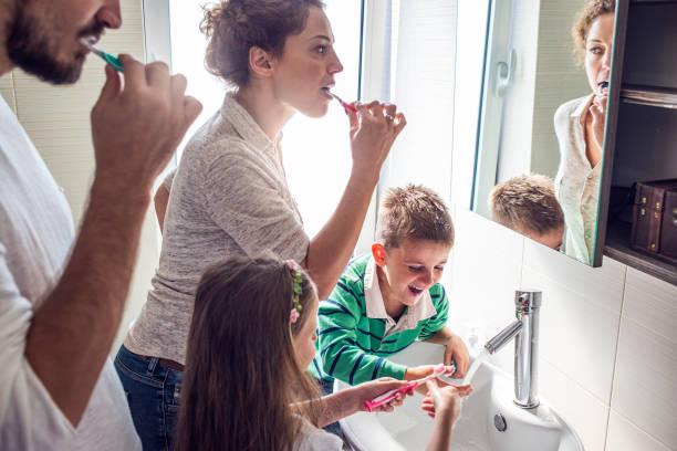 Famille nombreuse qui partage la salle de bain pour se brosser les dents