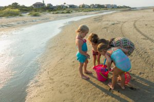 Petites filles en train de remplir un seau sur la plage