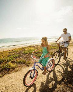 Père et sa fille en train de faire du vélo le long de l'océan
