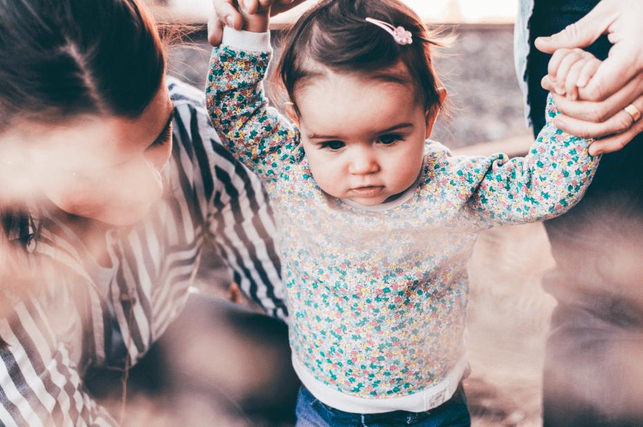 Petite fille apprenant à marcher en tenant les mains de ses parents