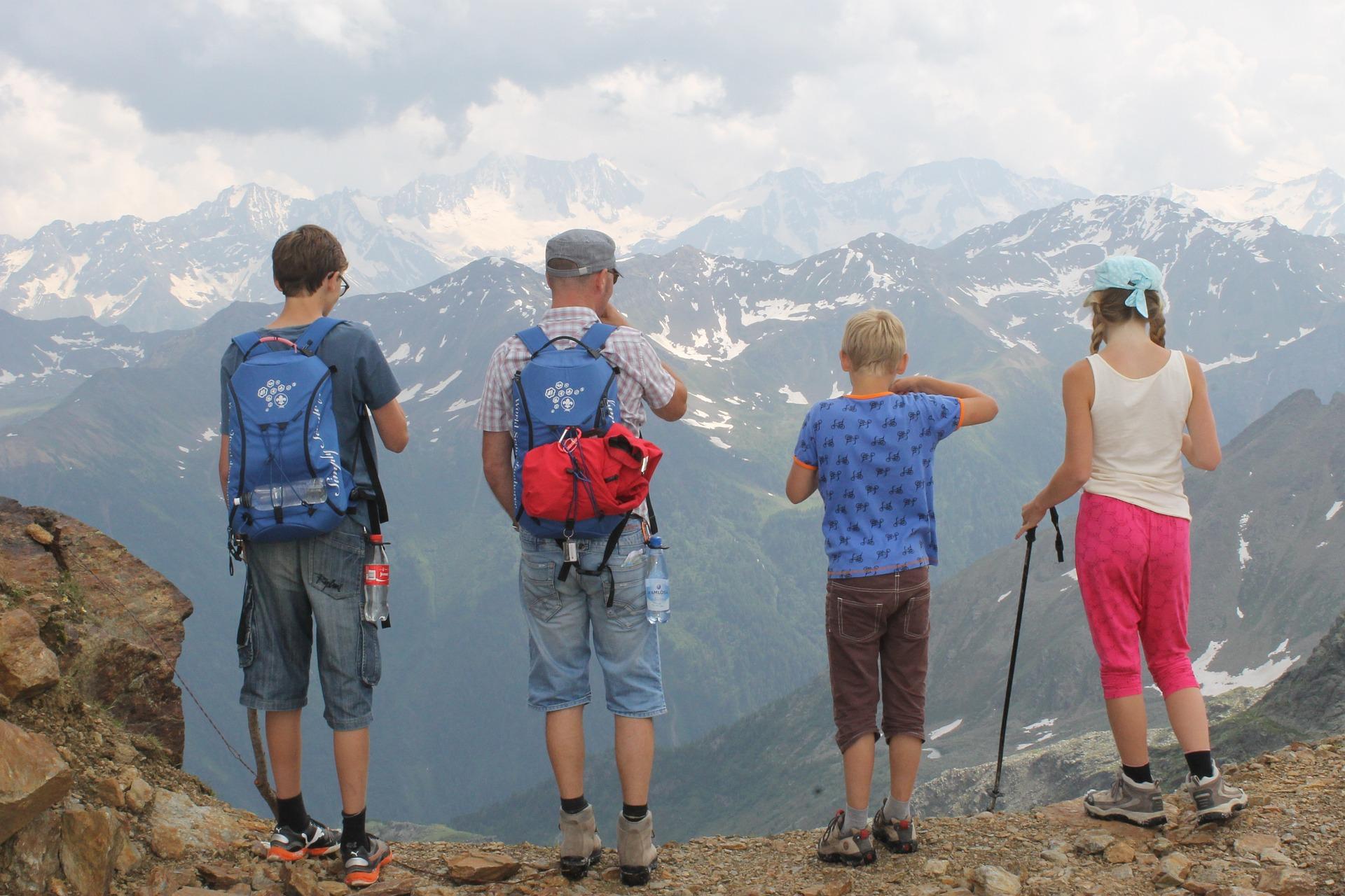 Membres d'une famille de dos au bord d'une falaise face une montagne enneigée