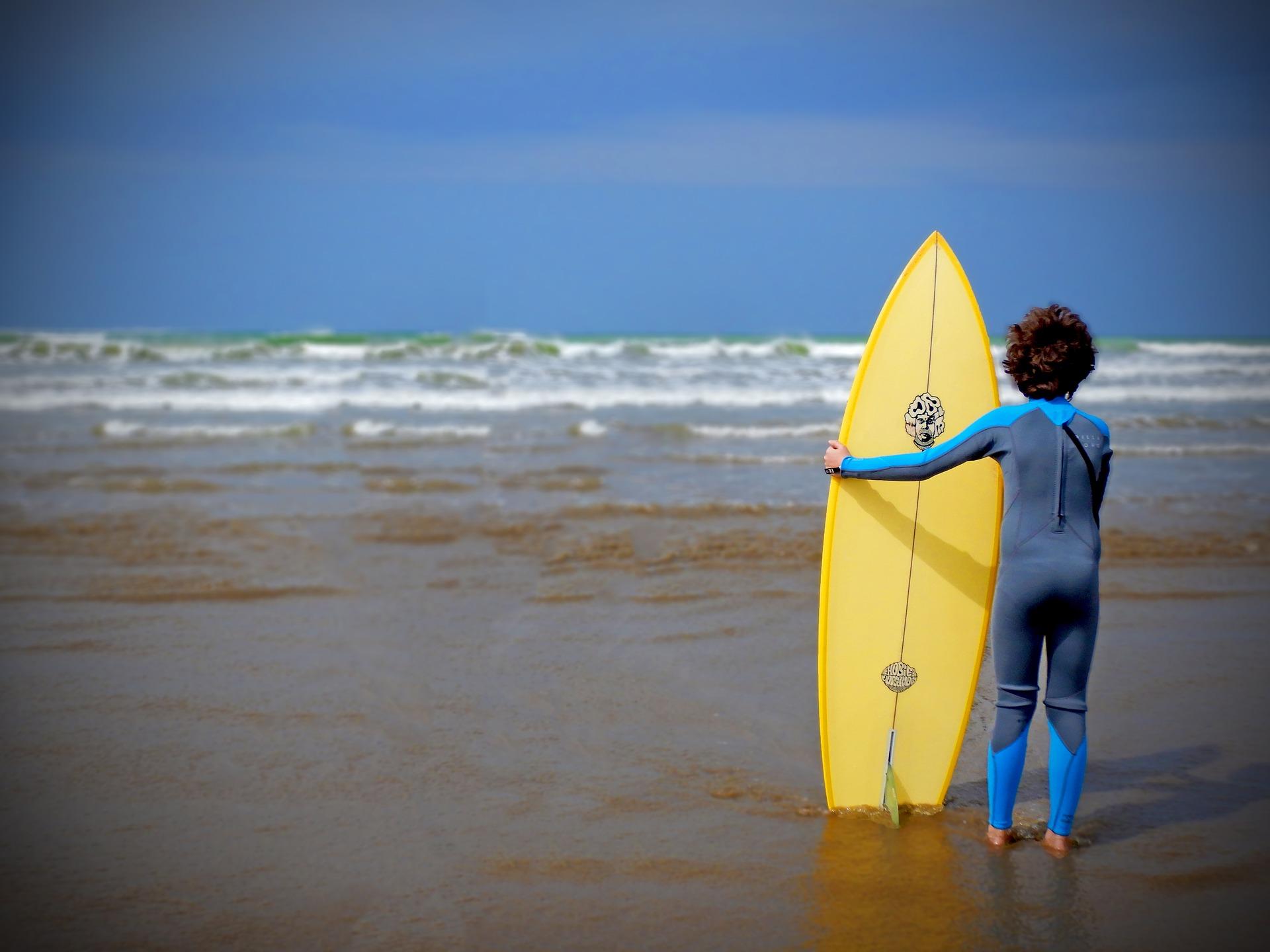 Une petit garçon sur la plage avec un surf