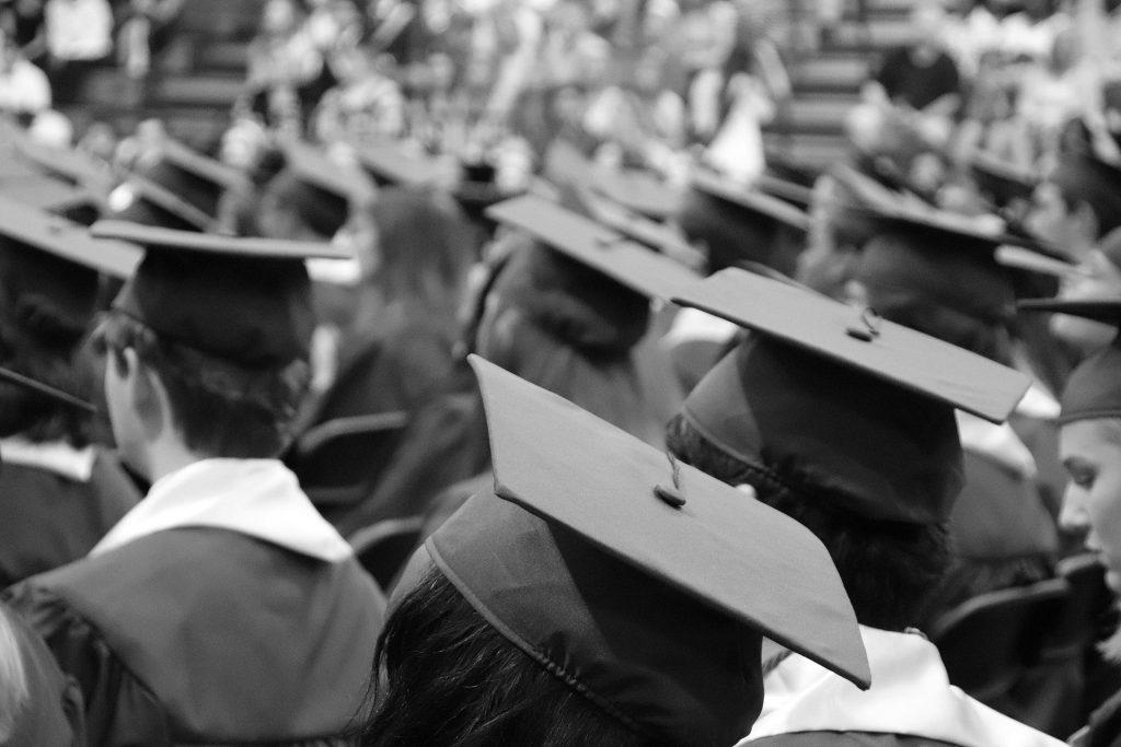 Etudiants vus de dos photographiés en noir et blanc à une cérémonie de remise de diplôme