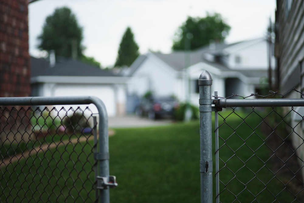 zoom sur un portail de maison ouvert avec maison floue en arrière plan