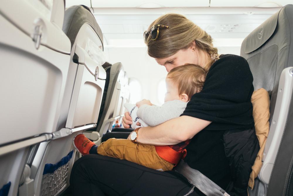 maman assise dans un avion tenant son bébé sur les genoux