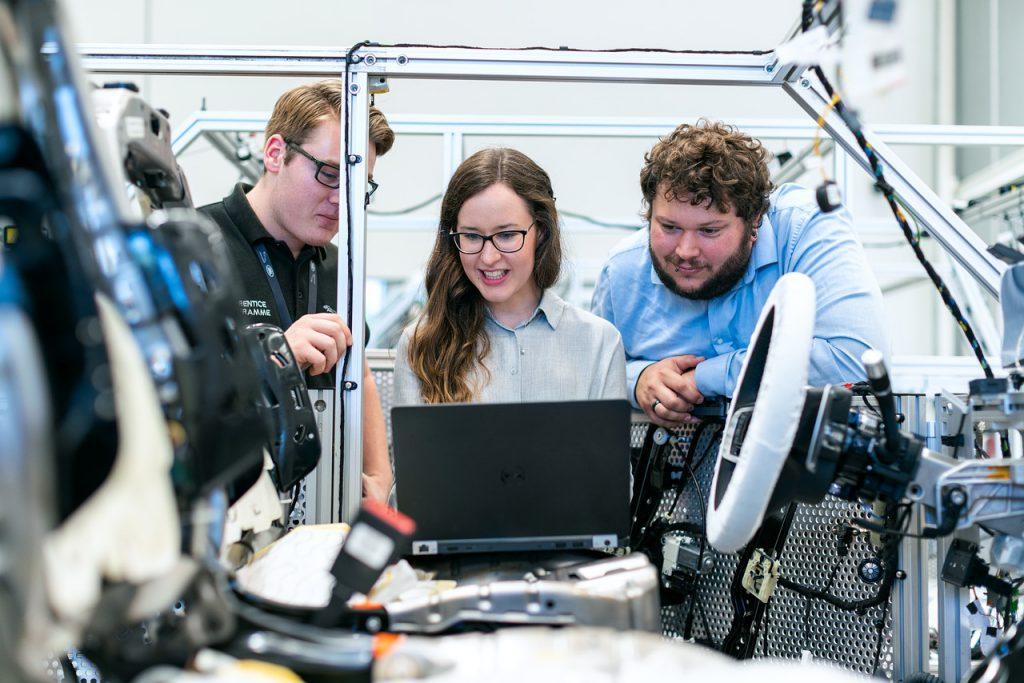 3 ingénieurs devant un ordinateur dans une unité de production