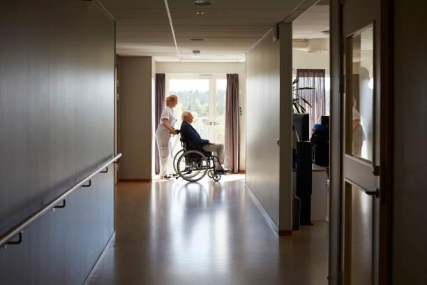 Personne âgée se déplaçant en fauteuil roulant dans une maison de retraite