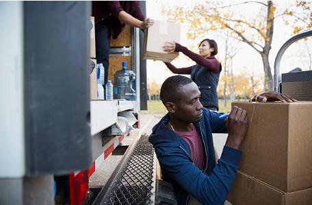 personnes qui chargent et déchargent des cartons d'un camion de déménagement
