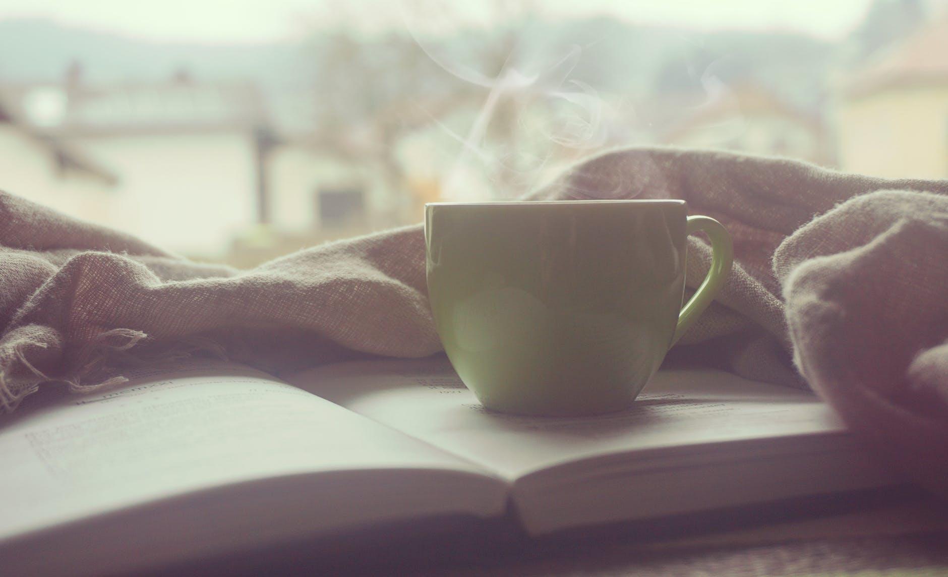 Jeune maman qui s'est préparé un thé et un livre pour s'accorder du temps pour soi
