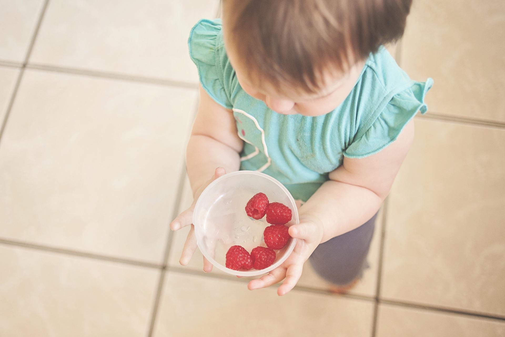 Un enfant en tee-shirt bleu en train de amnger des fruits