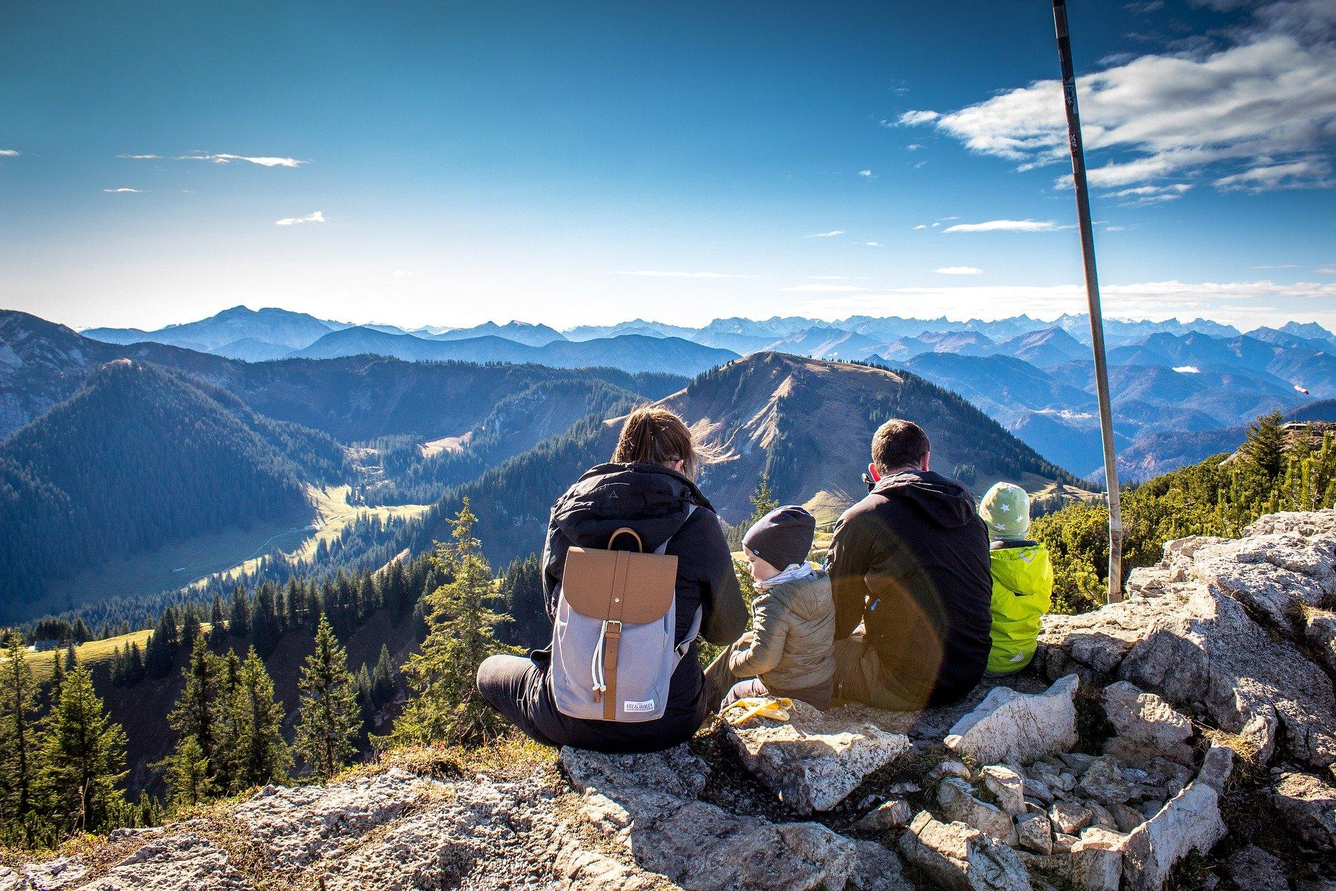 Vue de dos d'une famille qui est assise tout en haut d'une falaise et qui regarde le panorama
