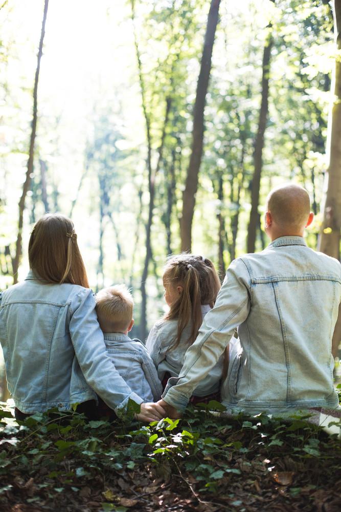 famille de 4 personnes portant ds vestes en jean assise dans une forêt